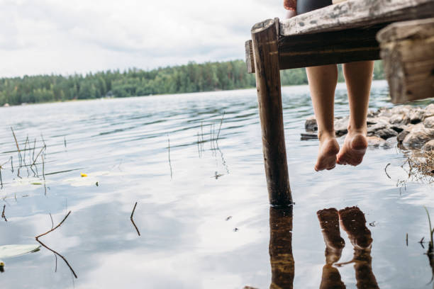 女人坐在碼頭上 - 芬蘭 個照片及圖片檔