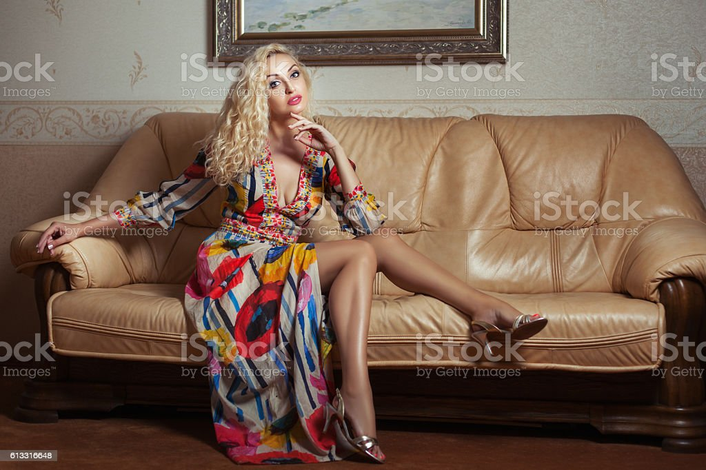 Woman sitting on a leather couch. stock photo