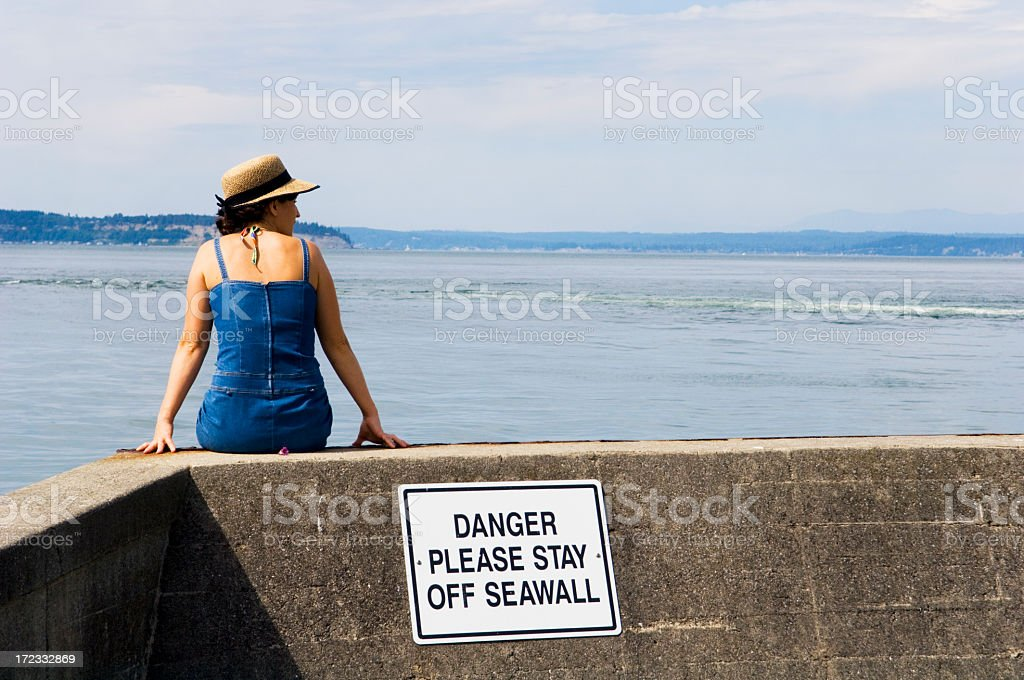Woman sitting on a ledge next to the ocean stock photo