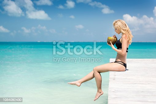 Woman sitting on a pier drinking a fresh coconut on vacation, Cancun, Mexico. Nikon D810. Converted from RAW.