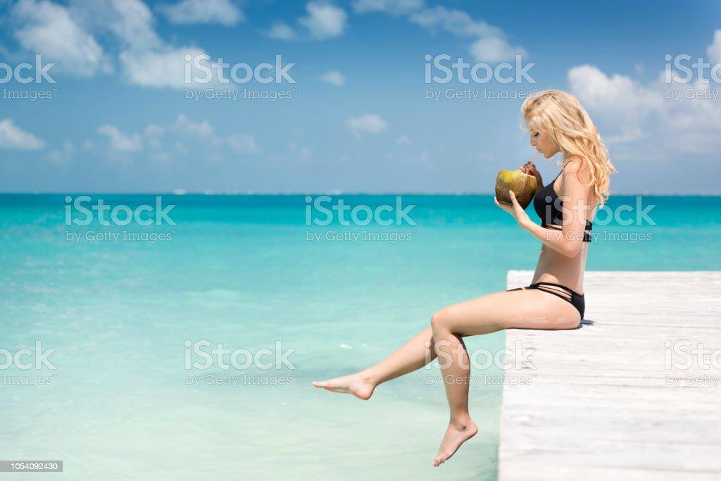 Frau sitzt auf einem Pier eine frische Kokosnuss trinken, im Urlaub, Cancun, Mexiko – Foto