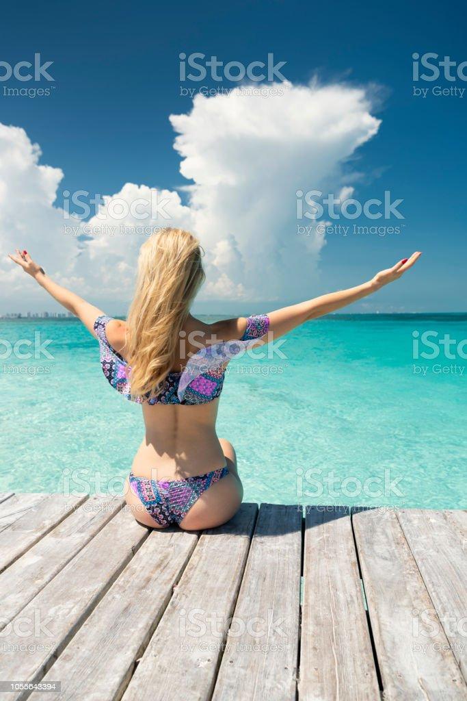 Frau sitzt auf einer Mole im Urlaub mit Blick auf das türkisblaue Meer, Cancun, Mexiko – Foto