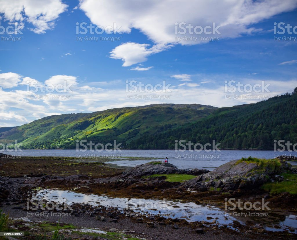 Woman sitting on a rock looking off into the distance in Scotland stock photo