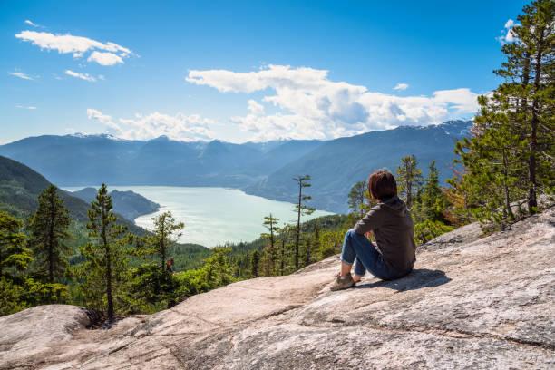 Frau sitzt auf einem Felsen auf dem Gipfel eines Berges bewundern die spektakuläre Landschaft an einem sonnigen Sommertag – Foto
