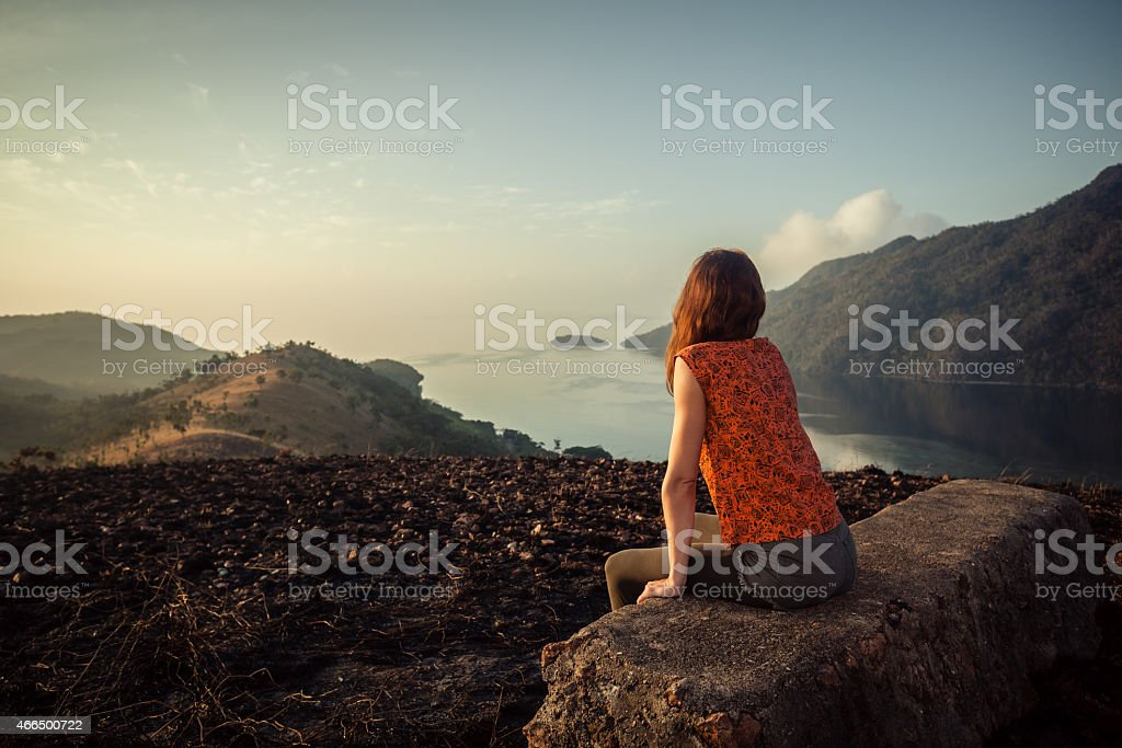 Woman sitting on a rock overlooking landscape at sunrise stock photo