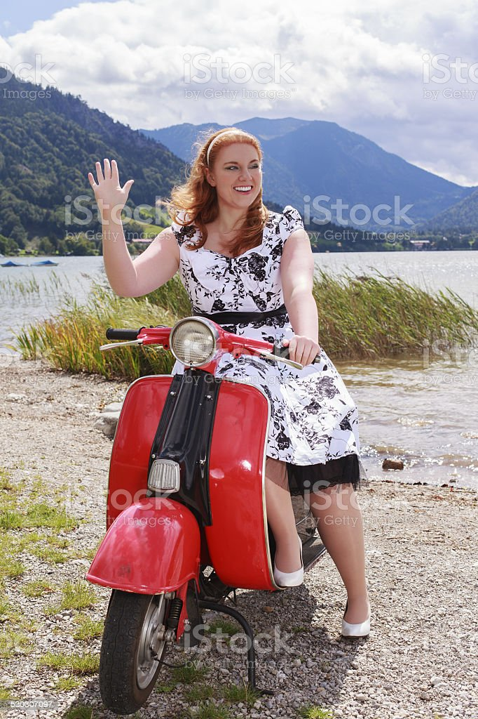 woman sitting on a scooter with a petticoat dress stock photo