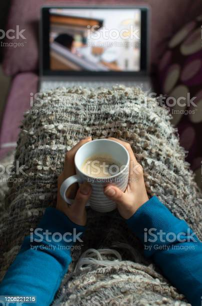Photo of Woman sitting on a sofa with a coffee cup and covered with a blanket watching a serie or video on a laptop.