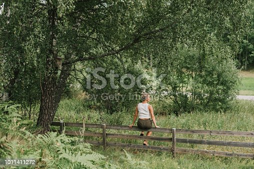 Woman sitting on a wooden fence by a beautiful tree in her rural garden Photo taken outdoors in summer in natural light