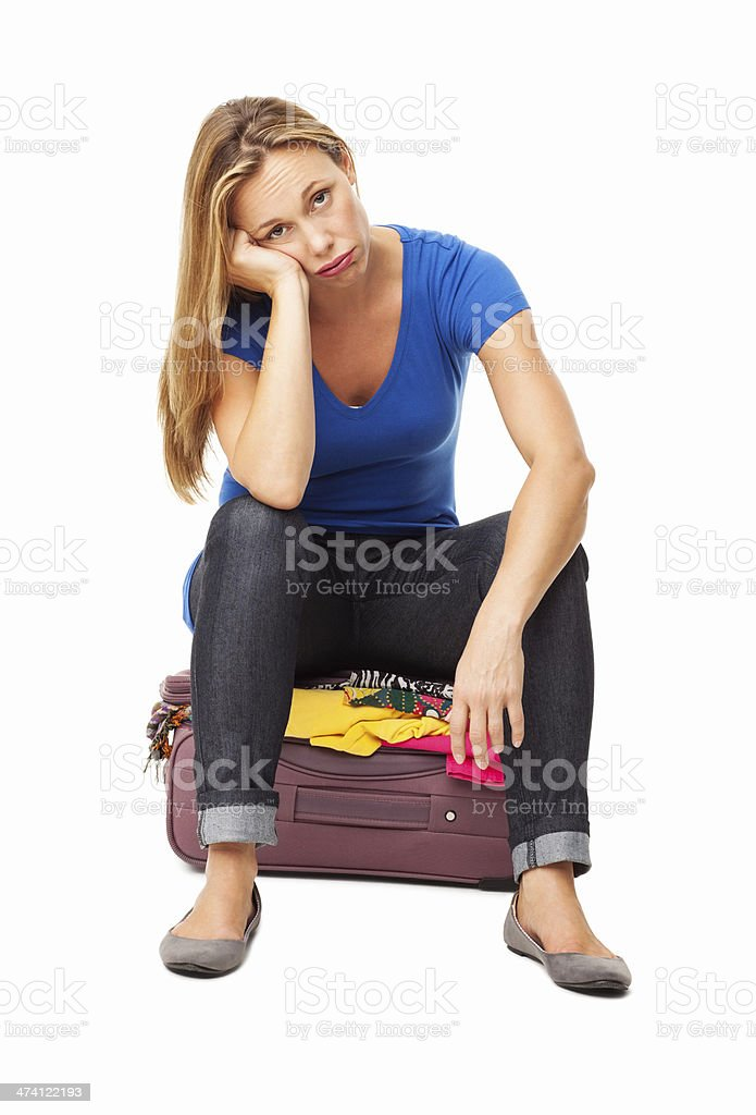 Woman Sitting On An Over-Stuffed Suitcase - Isolated royalty-free stock photo