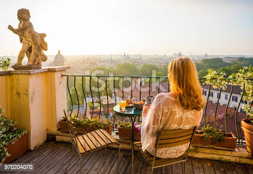 Unrecognizable woman sitting on balcony in early morning