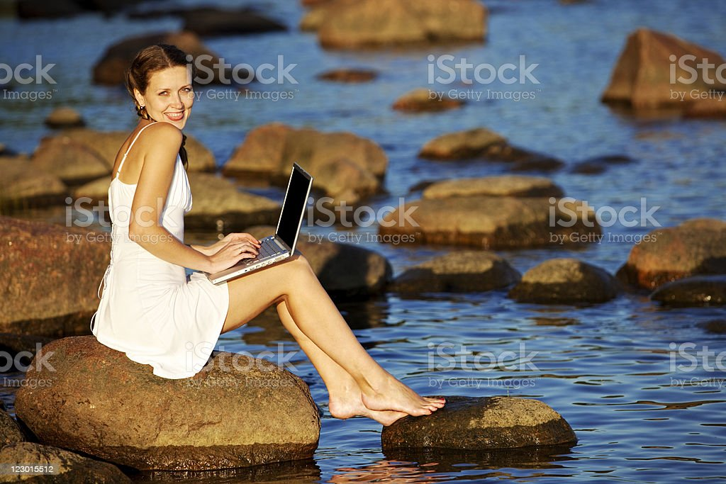 Woman Sitting on Beach and Using Laptop royalty-free stock photo