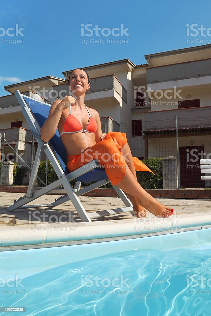 Woman sitting on beach chair near pool and smiling stock photo
