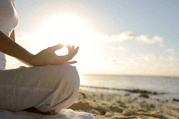 Woman Sitting On Beach With Yoga Lotus Position stock photo