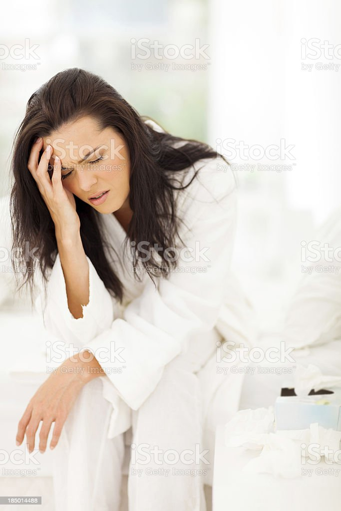 woman sitting on bed and having headache royalty-free stock photo