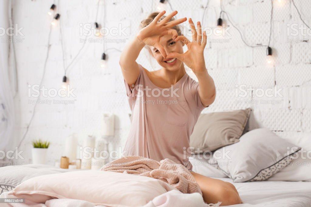 Frau sitzt auf dem Bett und zeigt Geste Herz mit Fingern - Lizenzfrei Auge Stock-Foto