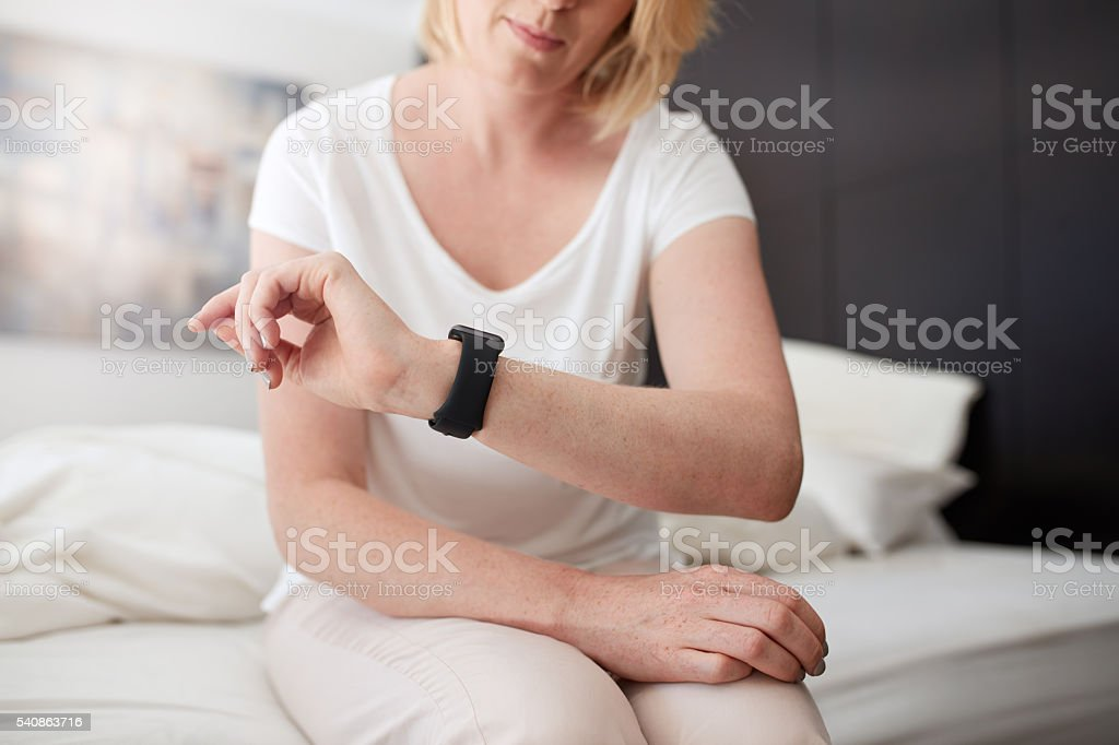 Woman sitting on bed checking time - foto de acervo
