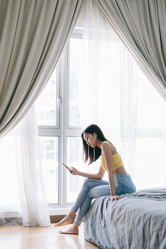 istock Woman sitting on bed using her smartphone 979629552