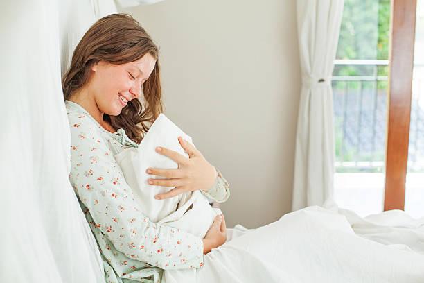 Frau sitzt auf dem Bett mit Ihrem Neugeborenen Kind – Foto