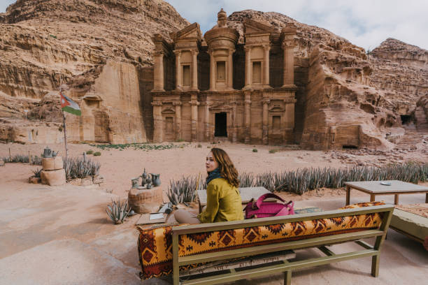 Woman sitting on bench  and looking at Monastery in Petra stock photo