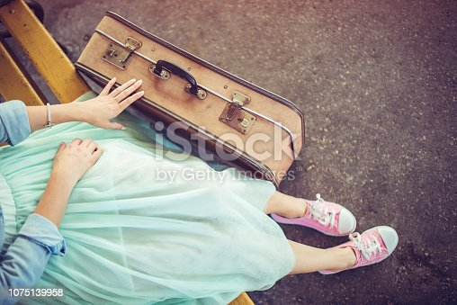 Woman sitting on bench and waiting for a train. Shot from above.