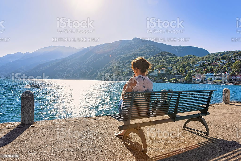 Woman sitting on bench at Ascona expensive resort stock photo