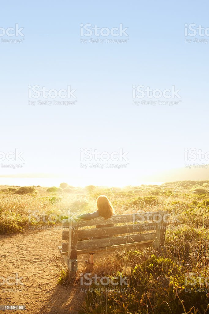 Woman sitting on bench in nature stock photo