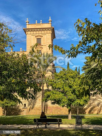Valencia, Spain - November 12, 2020: Woman sitting on bench in front of old tower in the Turia Garden. This dried riverbed converted into public park is the preferred place to go to take a city break
