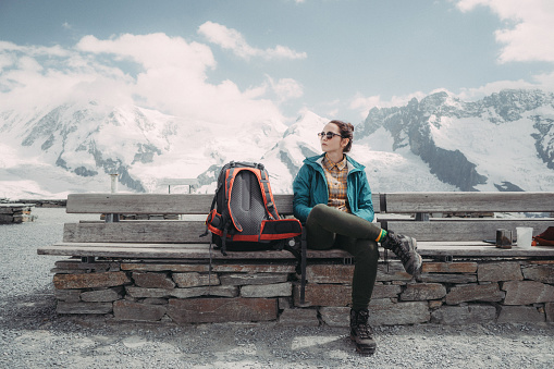 istock Woman sitting on bench on the background of  the glacier in Swiss alps 1059318152