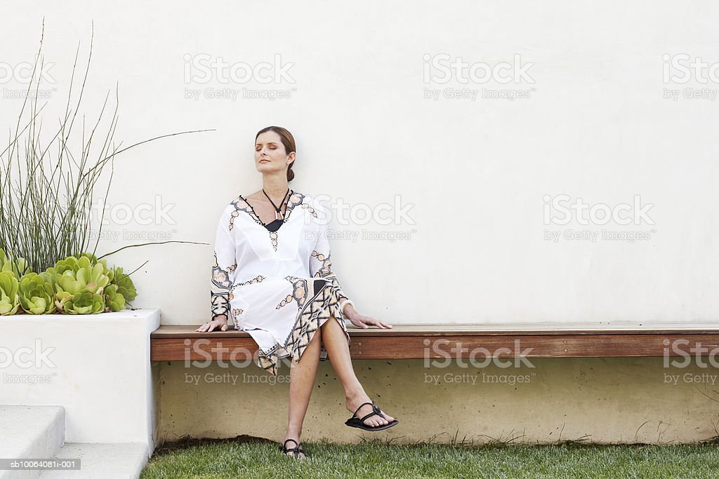 Woman sitting on bench outside house royalty-free stock photo