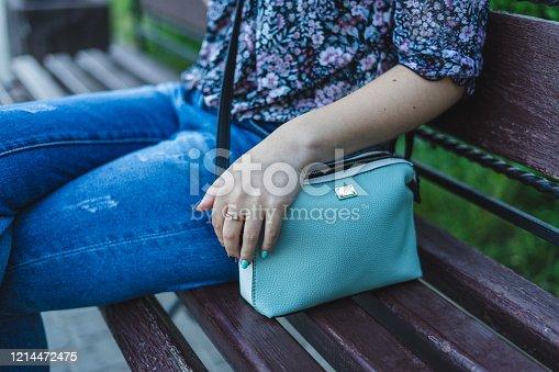 532274156 istock photo Woman sitting on bench with handbag. 1214472475