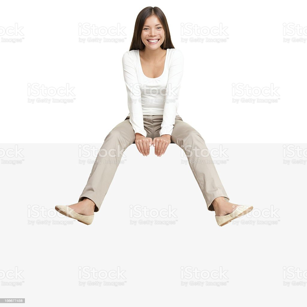 Woman sitting on billboard sign edge stock photo