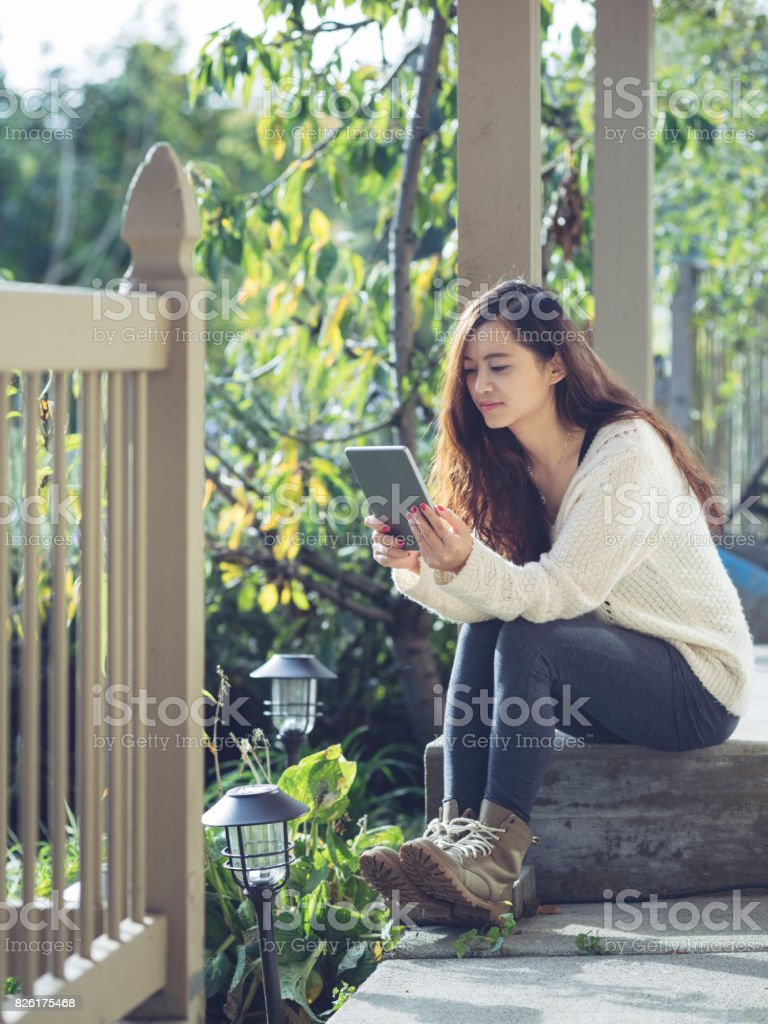 woman sitting on concrete porch step with holding tablet stock photo