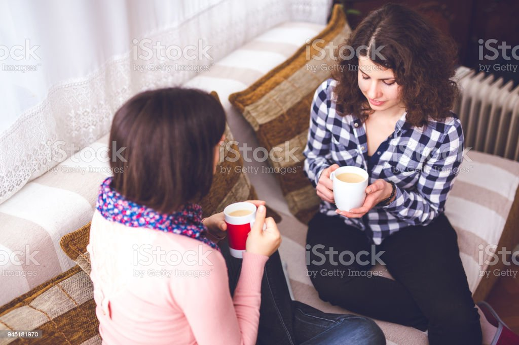 Woman sitting on couch and drinking coffee with his worried girlfriend. stock photo