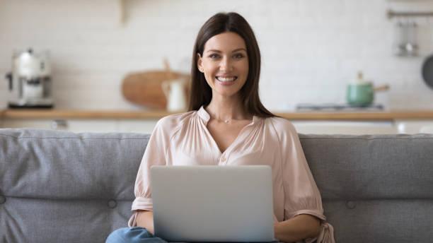 坐在沙發上拿著電腦看相機的女人 - small business saturday 個照片及圖片檔