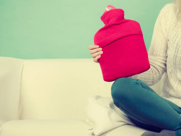 Woman sitting on couch holding hot water bottle Warming up during cold winter or autumn days. Woman sitting on couch holding hot water bottle hot water bottle stock pictures, royalty-free photos & images