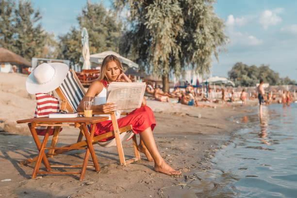 vrouw zittend op een ligstoel en krant lezen - newspaper beach stockfoto's en -beelden