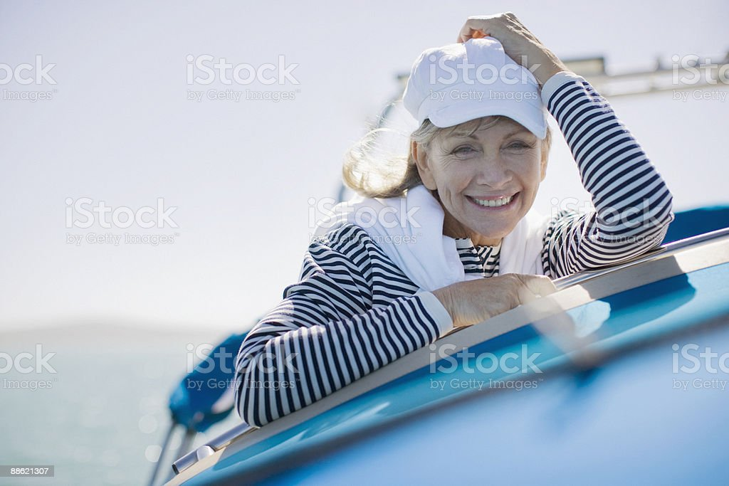 Woman sitting on deck of boat stock photo