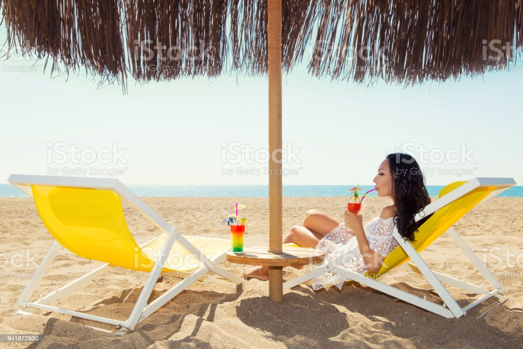 Woman sitting on deckchair and enjoying a cocktail on a tropical beach стоковое фото