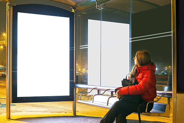 woman sitting on desk at bus stop - bushalte stockfoto's en -beelden