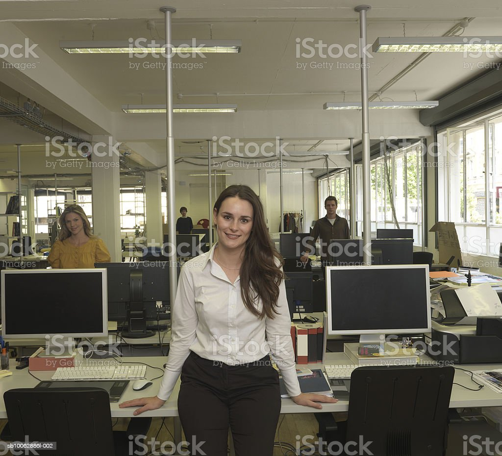 Woman sitting on desk, smiling, portrait, colleagues in background foto de stock royalty-free