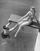 Woman sitting on diving board, man grasping her hand (B&W), elevated view