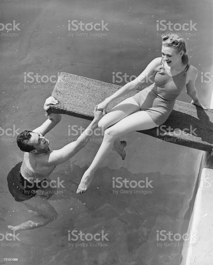 Woman sitting on diving board, man grasping her hand (B&W), elevated view stock photo