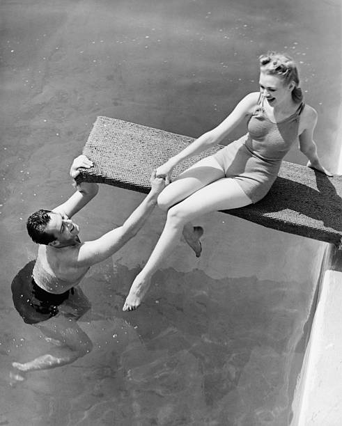 woman sitting on diving board, man grasping her hand (b&w), elevated view - vintage stock photos and pictures