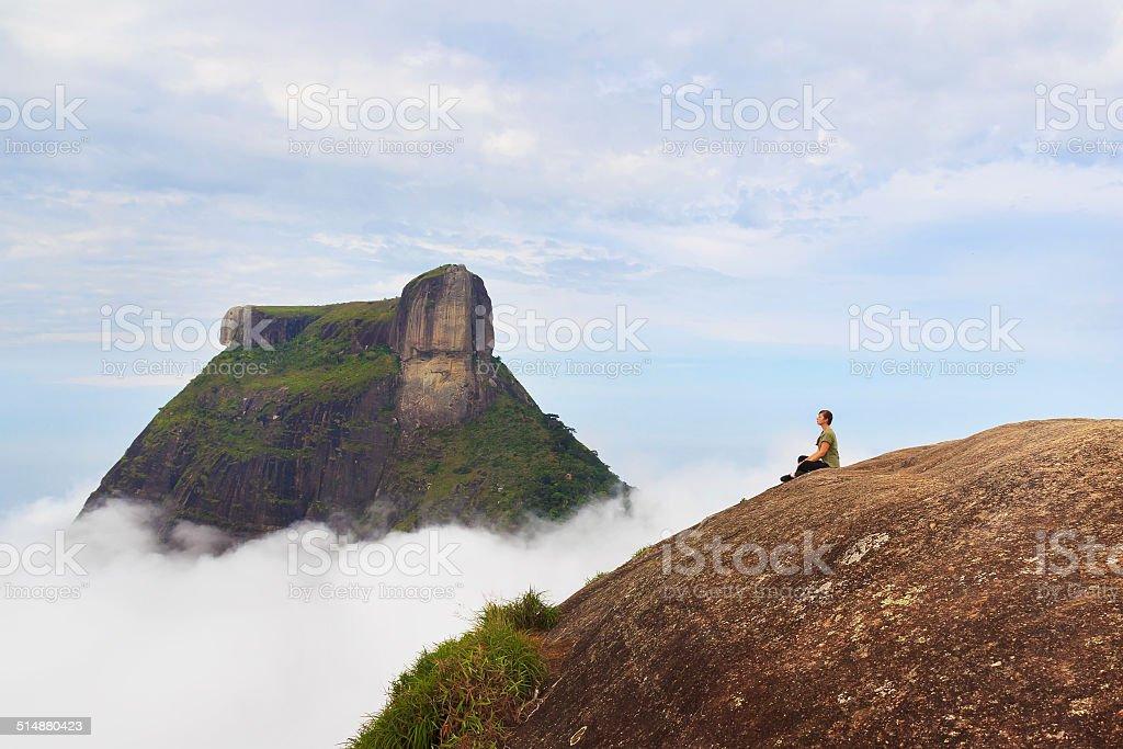 Woman sitting on edge mountain Pedra Bonita, Rio de Janeiro, stock photo