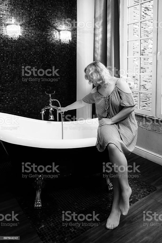 Mulher sentada na beirada da banheira foto royalty-free