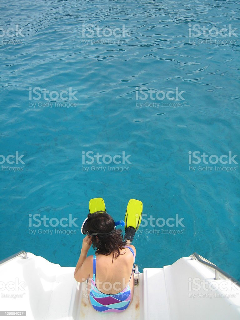 Woman sitting on edge of boat with flippers and snorkle royalty-free stock photo