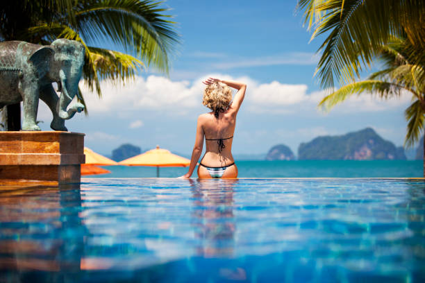 Frau sitzt am Rand des infinity-pool, Rückansicht – Foto