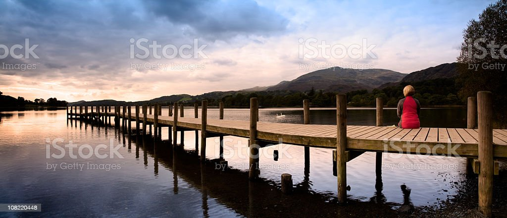 Woman Sitting on Edge of Lake Dock at Sunset royalty-free stock photo