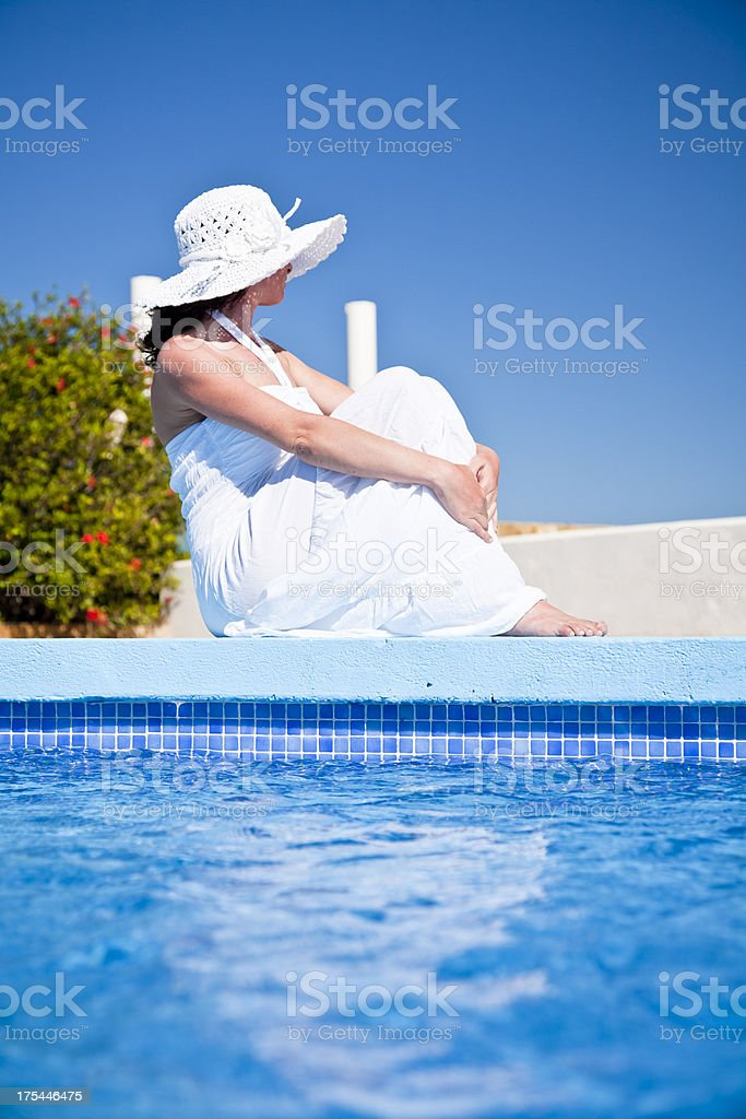 Woman sitting on edge of swimming pool royalty-free stock photo