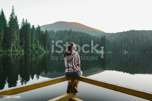 Young Caucasian woman sitting on fence and looking at  Synevir lake